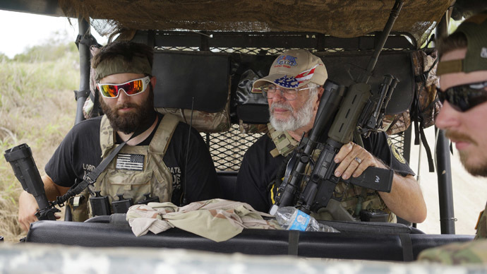 """Members of the """"Patriots"""" Huggie Bear (L, not his real name), Ray (C, no last name given) and Will (R, no last name given) patrol in their UTV near a camp of patriots near the U.S.-Mexico border outside Brownsville, Texas September 2, 2014. (Reuters/Rick Wilking)"""