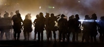 Aug. 12, 2014: Protesters line the street as police stand watch in Ferguson, Mo.AP
