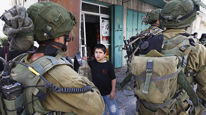 A Palestinian boy looks at Israeli soldiers as they patrol in the West Bank city of Hebron (Reuters / Ammar Awad)