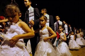 Palestinians participate in a mass wedding of hundreds of Palestinians in the town of Beit Lahiya, northern Gaza Strip, Thursday, July 30, 2009. Over 400 couples were married on Thursday in Beit Lahiya in a ceremony sponsored by Hamas. (AP Photo/Khalil Hamra)