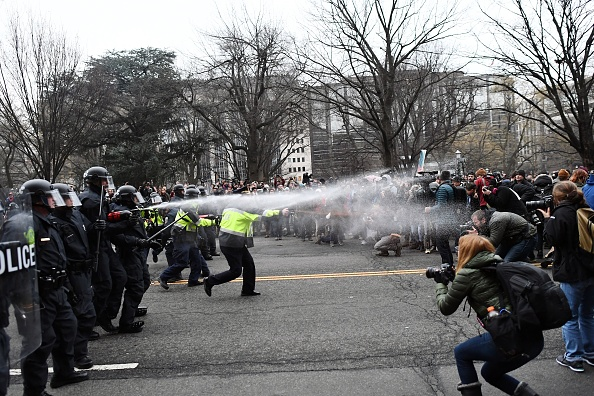 Police pepper spray at anti-Trump protesters during clashes in Washington, DC, on January 20, 2017.  Masked, black-clad protesters carrying anarchist flags smashed windows and scuffled with riot police Friday in downtown Washington, blocks away from the route of the parade in honor of newly sworn-in President Donald Trump. Washington police arrested more than 90 people over acts of vandalism committed on the fringe of peaceful citywide demonstrations being held against Trump's inauguration. / AFP / Jewel SAMAD (Photo credit should read JEWEL SAMAD/AFP/Getty Images)