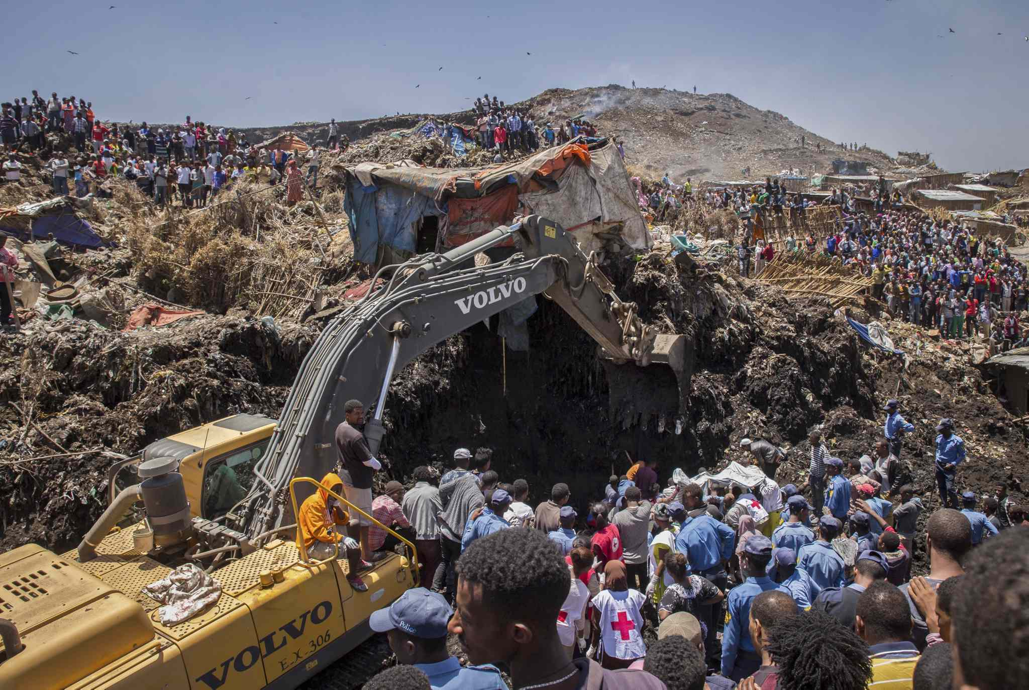 In this Sunday, March 12, 2017 photo, rescuers work at the scene of a garbage landslide, on the outskirts of the capital Addis Ababa, in Ethiopia. A mountain of trash gave way in a massive garbage dump on the outskirts of Ethiopia's capital, killing dozens and leaving more missing, residents said.