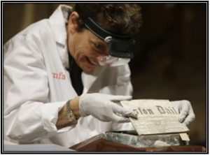 Hatchfield removes a folded newspaper from more than 200 years ago found in the time capsule Tuesday in Boston. None of the newspapers were opened to better preserve the ancient paper