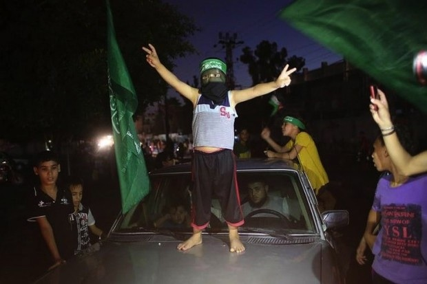 A Palestinian child wearing a Hamas headband flashes the sign of victory atop a car as people gather in the streets to celebrate after a deal reached between Hamas and Israel over a long-term end to seven weeks of fighting, Aug. 26, 2014 in Rafah in the southern of Gaza Strip. (Said Khatib/AFP/Getty Images)