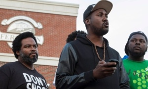Community activists Montague Simmons and Tory Russell listen as rapper Tef Poe speaks during a rally in Ferguson. Photograph: Whitney Curts/Reuters
