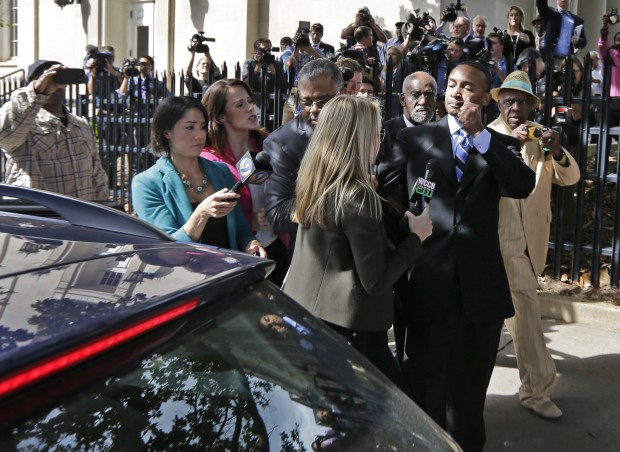 Former Charlotte Mayor Patrick Cannon, right, leaves the federal courthouse in Charlotte, N.C., Tuesday, Oct. 14, 2014 after being sentenced to 44 months in prison. In a deal with prosecutors, Cannon pleaded guilty in June to one count of honest services wire fraud. (AP Photo/Chuck Burton)