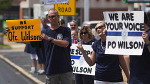 Supporters of officer Darren Wilson hold placards outside Barney's Sports Pub in St. Louis, Missouri August 23, 2014. (Reuters/Adrees Latif)