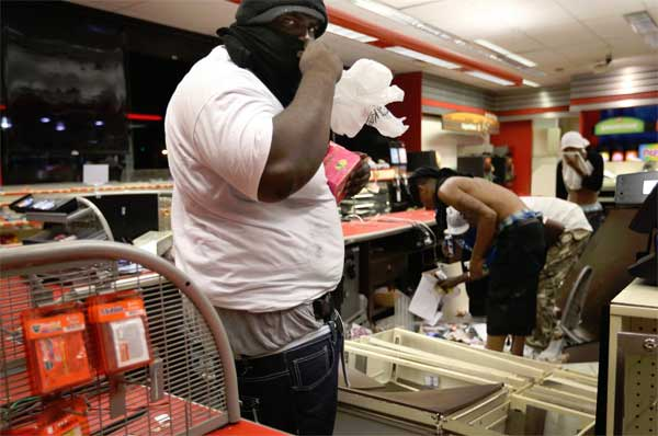 Black Rioters protest by robbing local convenience stores. A man armed with a gun in his waistband takes items inside the QuikTrip convenience store in Ferguson, Missouri.