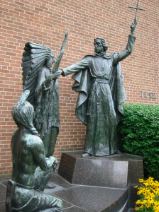 Jesuit missionary priest praying over American Indians