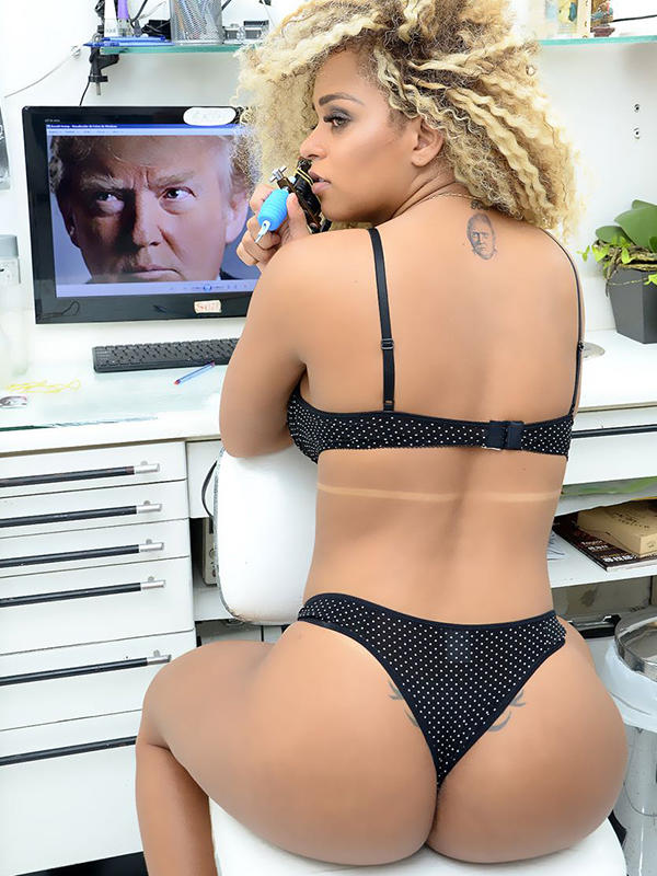 """Brazilian booty queen Erika Canela, recently crowned Miss Bumbum, has a soft spot for US President-elect Donald Trump... above her famous derriere. The model shocked her fans by getting the controversial business mogul's face TATTOOED on her back. America's new president has been the butt of many jokes, but this 'Trump Stamp' has him overlooking possibly the most famous rear in the world. And as an admirer of beauty pageants and their contestants, having ran Miss Universe for many years, one would expect Trump to be flattered by the move. """"I'm a big fan of his,"""" said Erika. """"People say 'you are crazy', but a lot of people liked it too. I think it's different, I love it!"""" The 24-year-old said she spent 2 """"painful"""" hours with an artist in Sao Paulo getting inked. Erika even reached out to Trump himself with a message, on his favourite method of communication, Twitter. """"I would love to know what he thinks,"""" said Erika. She has endured racist trolling in Brazil after becoming the first black Miss Bumbum, but despite Trump's history of twitter attacks on individuals, she is still a fan. """"I've always been a fan of Trump, ever since The Apprentice,"""" she said. """"He is the perfect man, he has built an empire and is pre-destined for greatness. He doesn't drink, he says what he thinks, and those are qualities I admire. """"I thought it would be fun to get the tattoo."""" Pictured: Erika Canela Ref: SPL1422107 130117 Picture by: Splash News Splash News and Pictures Los Angeles:310-821-2666 New York:212-619-2666 London:870-934-2666 photodesk@splashnews.com"""